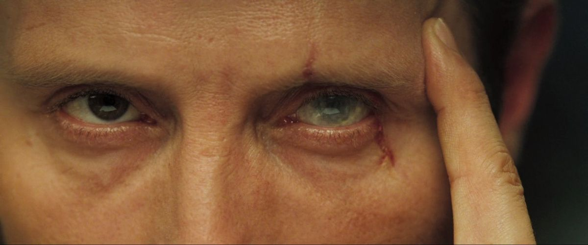 Le Chiffre holds a finger against his scarred eye in Casino Royale