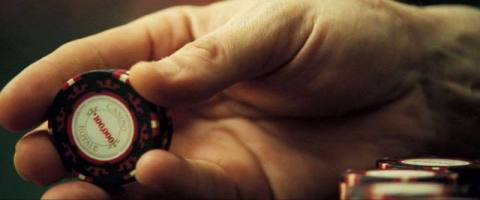 a close up of a hand holding a poker chip in Casino Royale