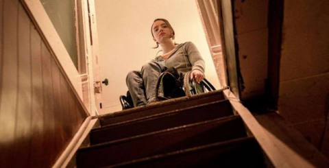 Kiera Allen, in a wheelchair, pauses at the top of a darkened staircase in Hulu's Run