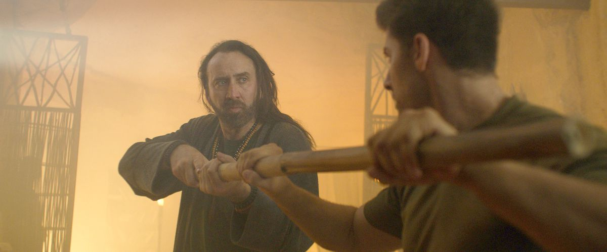 Nicolas Cage, with long ratty hair, faces off against Alain Moussi as they each grip opposite ends of a staff in Jiu Jitsu