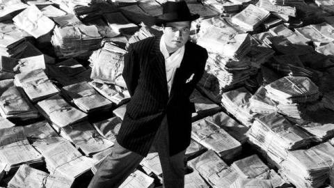 Orson Welles in Citizen Kane stands in front of a field of bundled newspapers