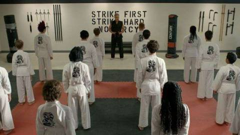 Sensei John Kreese, in a black gi, addresses his assembled students, in white, at Cobra Kai dojo.