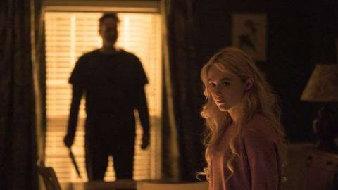 Vince Vaughn looms silhouetted against a window, holding a knife, as Kathryn Newton sits in the foreground in Freaky