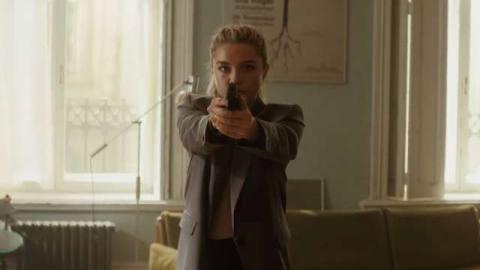Florence Pugh as Yelena Belova holding a gun at camera in Black Widow movie trailer