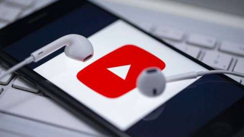 the YouTube logo being displayed on a smartphone that has white earbuds sitting on top of it