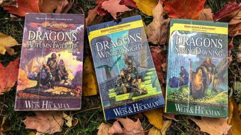 Three books on a bed of fallen leaves. Titled Dragons of Autumn Twilight, of Winter Night, and of Spring Dawning.