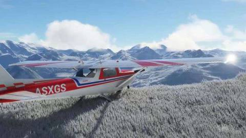A white Cessna with red livery on a snowy hilltop overlooking distant mountains.