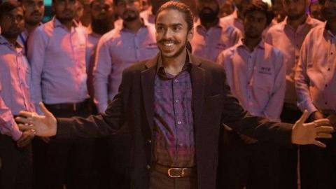Adarsh Gourav, in a plaid shirt and dark suit jacket, grins in front of a crowd of white-shirted men in THE WHITE TIGER​.