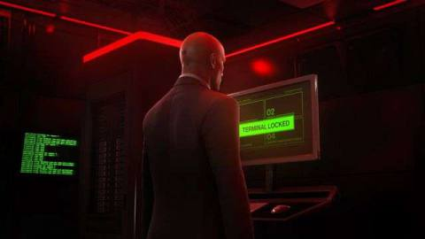 Agent 47 stands at a computer terminal in a server room in Dubai in Hitman 3