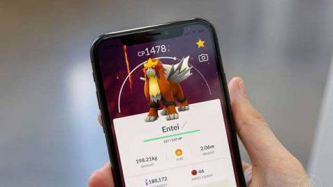 a close-up of a hand holding an iPhone with Pokémon Go running on it, with Entei visible on the screen