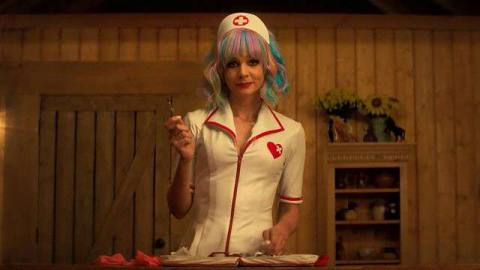 Cassie (Carey Mulligan) dressed as a nurse, holds a needle in a wood cabin bedroom.