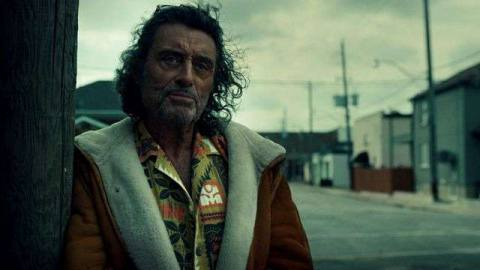 A battered-looking Ian McShane leans against a wall in American Gods