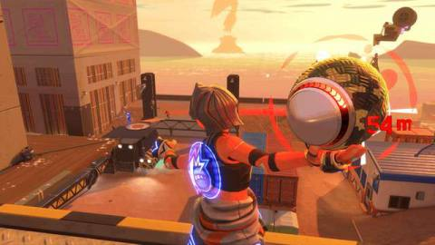 Seen from behind, a player winds up a dodgeball shot, aiming for an opponent across a rooftop in the distance