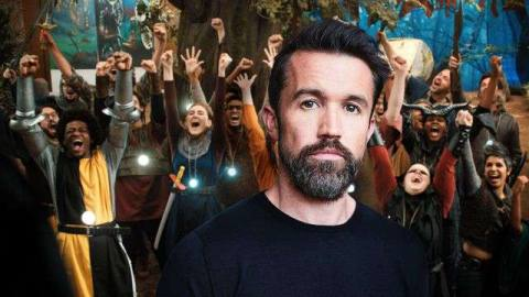Actor Rob McElhenney looks to camera with a large cheering group of people in medieval costume cheering behind him