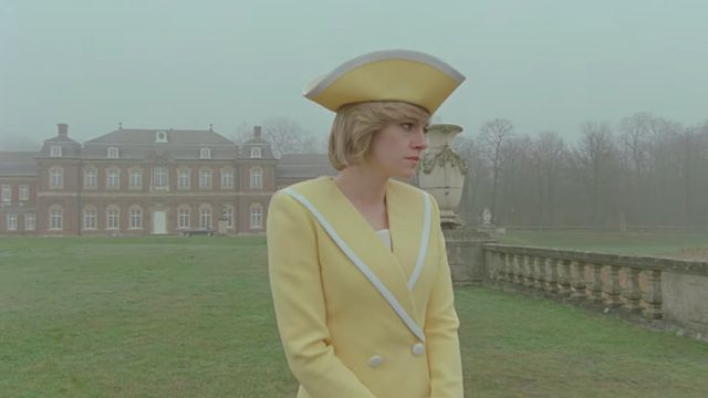 Kristen Stewart standing outdoors in yellow as Princess Diana in Spencer