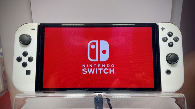 A photo of the Nintendo Switch (OLED Model) with the Switch logo