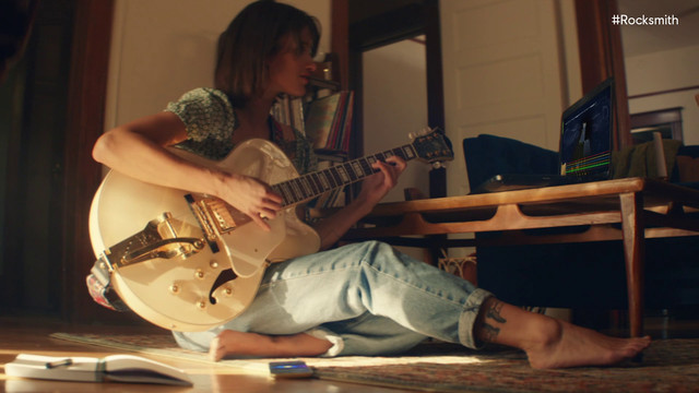 a woman sitting on the floor playing an electric guitar in a trailer for Rocksmith Plus