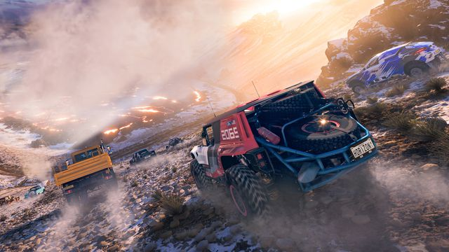 cars race down the side of a volcano, with patches of snow and steam rising in the distance, in Forza Horizon 5