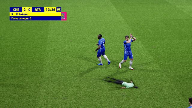 screenshot of a glitch in eFootball. The match official is face down, pressed into the pitch, while a Chelsea player applauds