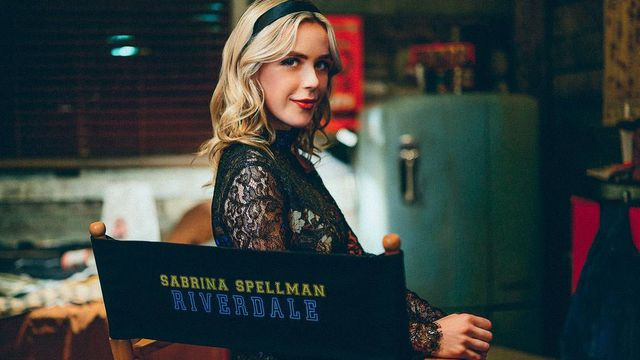 """Kiernan Shipka sits in a Riverdale set chair in her Sabrina costume giving a little smile that silently says """"I'm back."""""""
