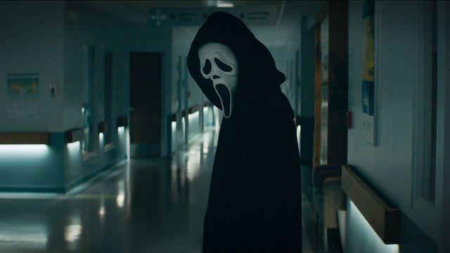 Ghostface stands in a high school hallway in Scream (2022)