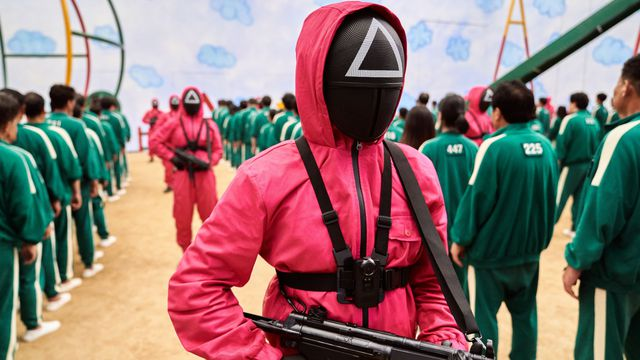 A group of masked men in pink jumpsuits brandishing assault rifles in Squid Game.