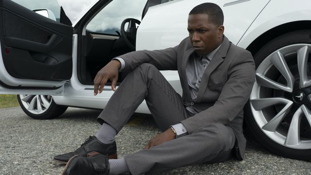 Leslie Odom Jr., in a nice grey suit, sits on the ground in front of his expensive-looking car and gets real pouty in Needle in a Timestack